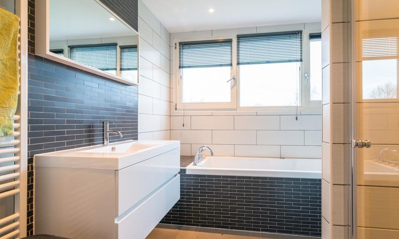 Badkamer met bruine marmerlook tegels leisteenlook en tegelstroken